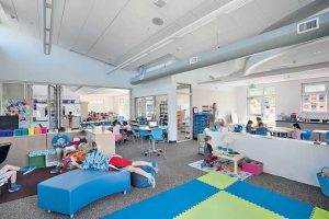 An adaptable learning environment at Cove Elementary School with moveable furniture and walls. A sliding glass door (background) allows two classrooms to become one.